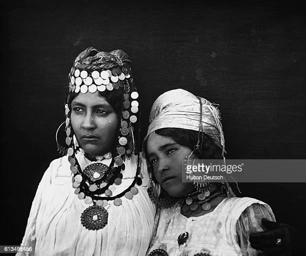 Two young women bedecked with metal jewelry and turban-style headdresses.