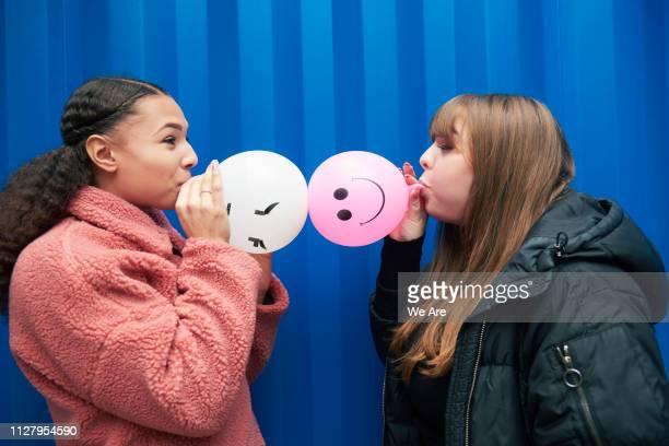 two young women blowing up balloons. - chaqueta rosa fotografías e imágenes de stock