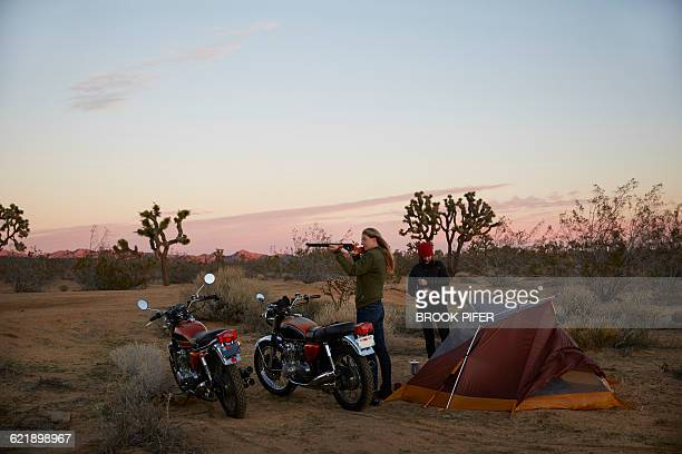 Two young women camping with motorcycles