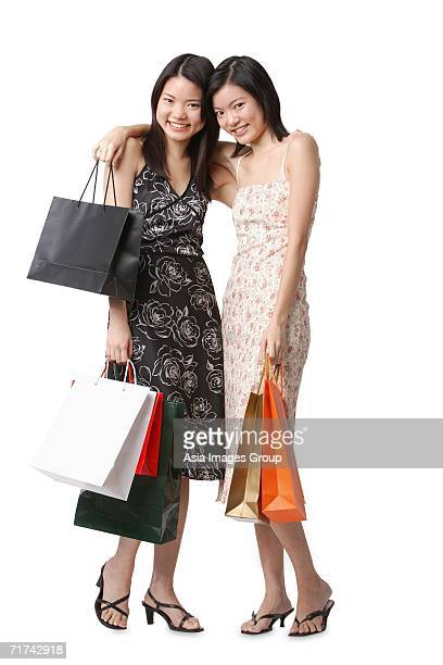 Two young women carrying shopping bags, arms around each other