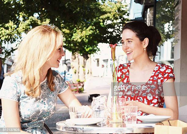 Two young women chatting at sidewalk cafe