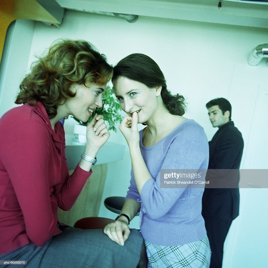 Two young women chatting, two men in background. : Stockfoto