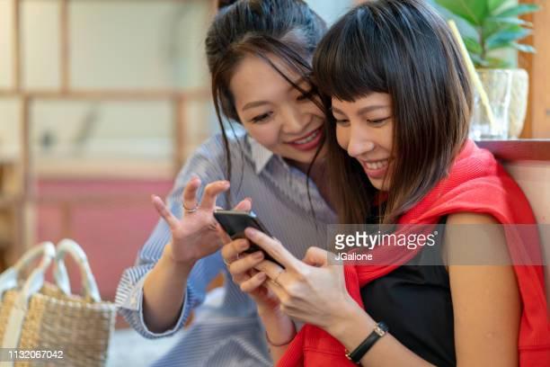 スマートフォンをチェックしている2人の若い女性 - トピックス ストックフォトと画像