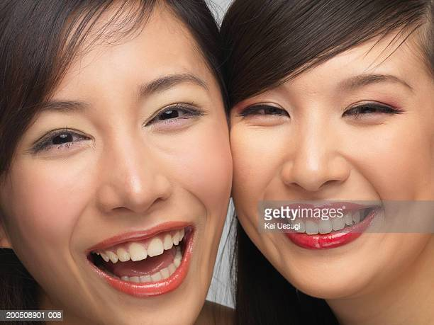 Two young women cheek to cheek, laughing, portrait