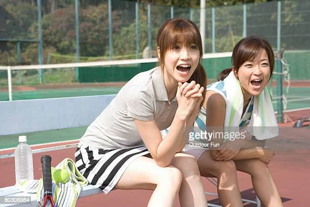 Two young women cheering in a tennis court