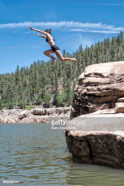 Two young women cliff jumping in the Blue Ridge Reservoir, Coconino National Forest, Arizona