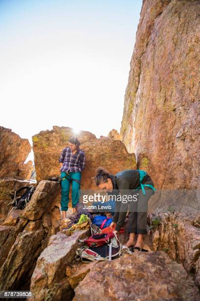 Two Young Women Climbers Prepare Gear as the Sun Rises Behind Coppery Colorado Rocks