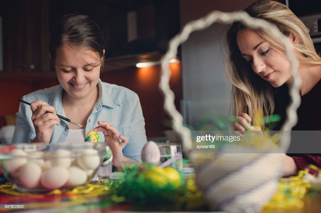 Two young women coloring eggs for Easter : Stock Photo