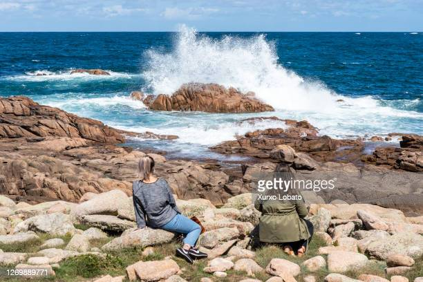 Two young women contemplate the oleja del mar on August 30, 2020 in Camariñas, Galicia, Spain. On the coast of this place is where the English navy...
