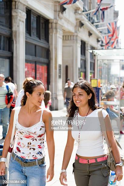 Two young women conversing while walking, smiling