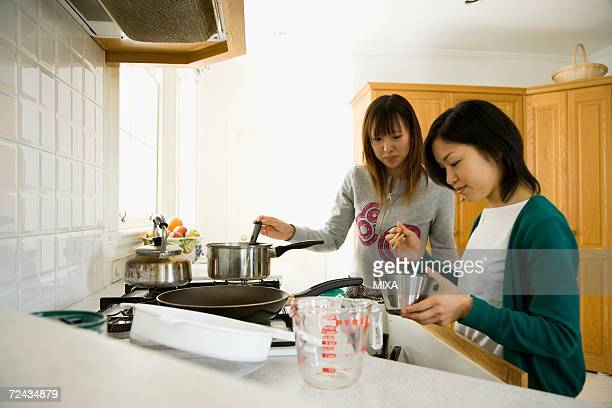 Two young women cooking in kitchen