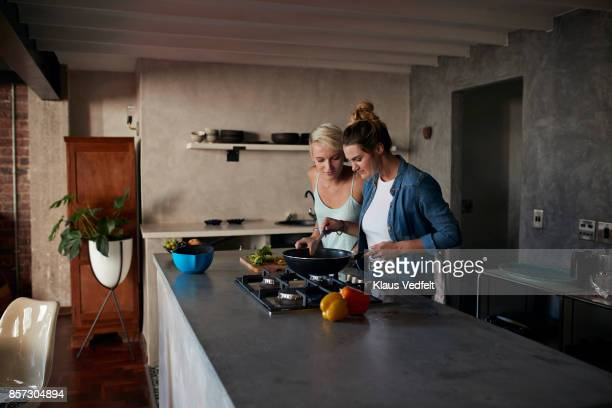 two young women cooking together in loft apartment - boca de fogão a gás - fotografias e filmes do acervo