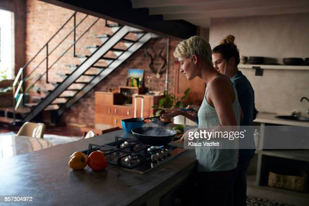 Two young women cooking together in loft apartment