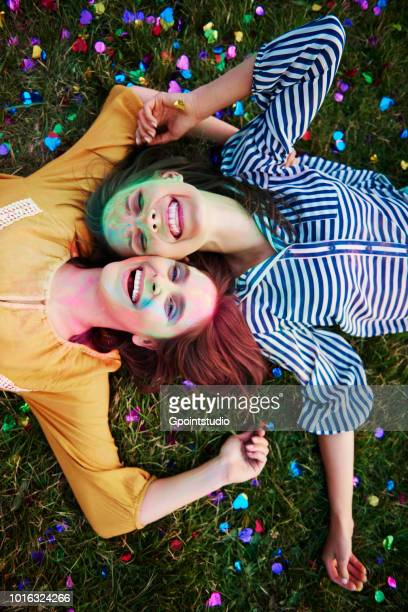 two young women covered in coloured chalk powder lying on grass at holi festival, overhead portrait - festival goer stock pictures, royalty-free photos & images