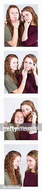 Two young women creating photo booth series of images in filmstrip format