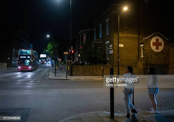 Two young women cross the road near a Red Cross building at night time in Hackney on May 9, 2020 in London, England. The UK is continuing with...