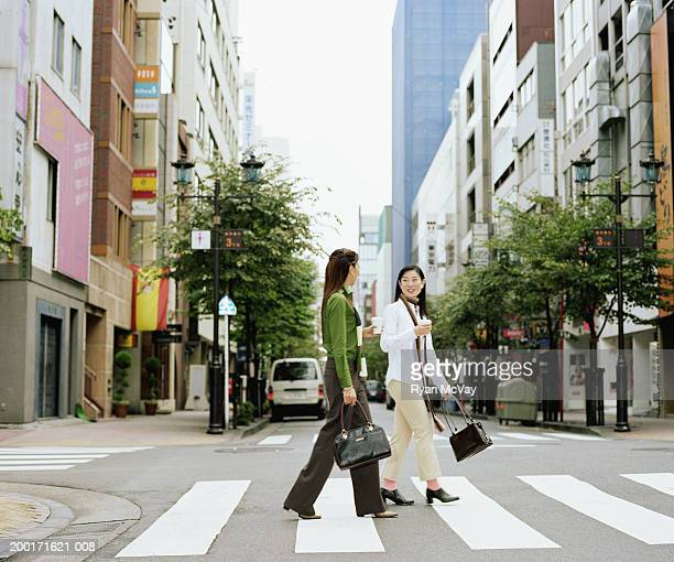 Two young women crossing urban street, having conversation, side view