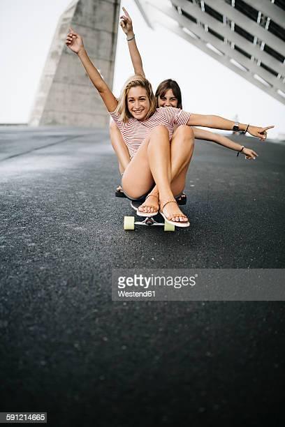 Two young women cruising on a longboard