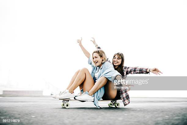 Two young women cruising on a longboard