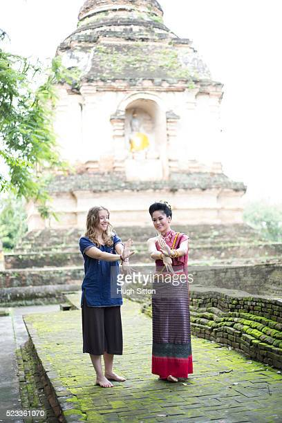 two young women dancing in front of thai temple, chiang mai, thailand - hugh sitton stock pictures, royalty-free photos & images