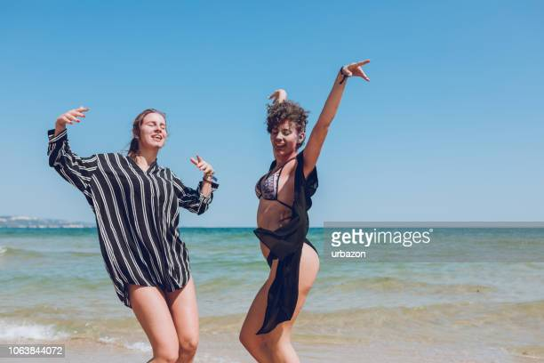 two young women dancing on the beach - cha cha stock photos and pictures