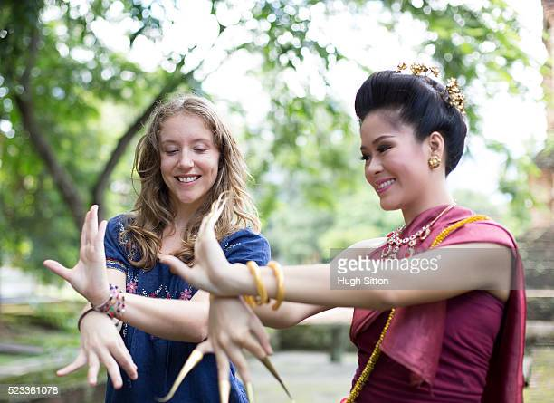 two young women dancing traditional thai dance, chiang mai, thailand - hugh sitton stock pictures, royalty-free photos & images
