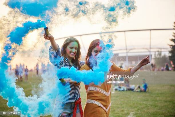 two young women dancing with blue smoke bombs at holi festival - music festival imagens e fotografias de stock
