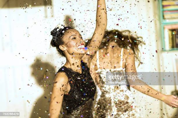 two young women dancing with confetti falling. - cocktail dress stock pictures, royalty-free photos & images