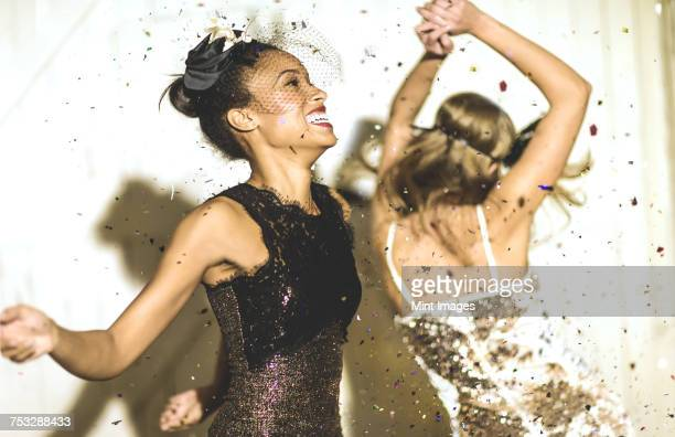 two young women dancing with confetti falling. - fascino foto e immagini stock