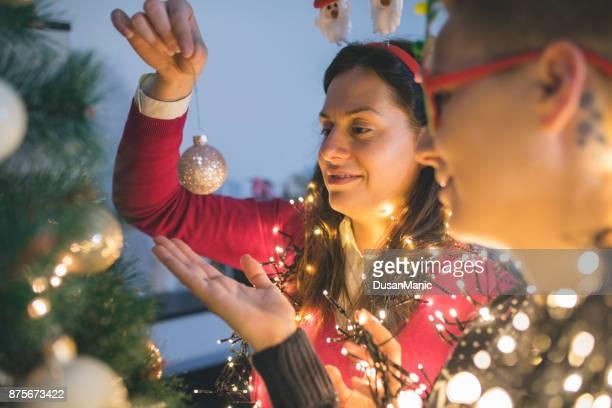 Zwei junge Frauen schmücken Weihnachtsbaum.