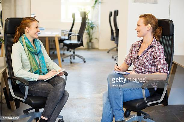 Two young women discussing business