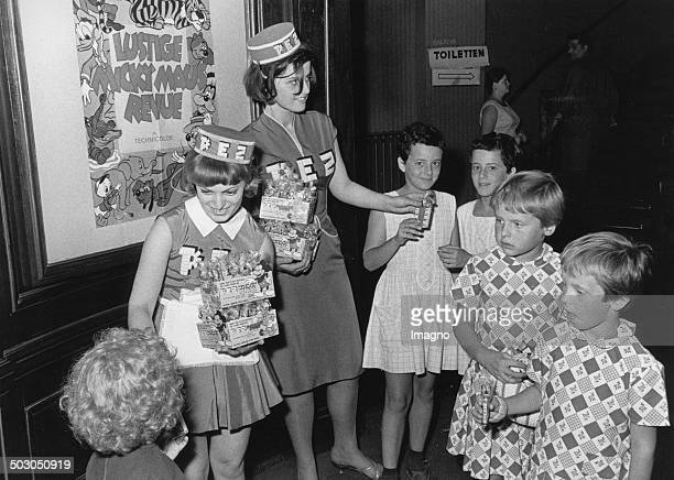 Two Young Women distribute PEZ candy in a movie theater Photograph 1964