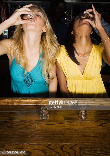 Two young women doing shots at bar