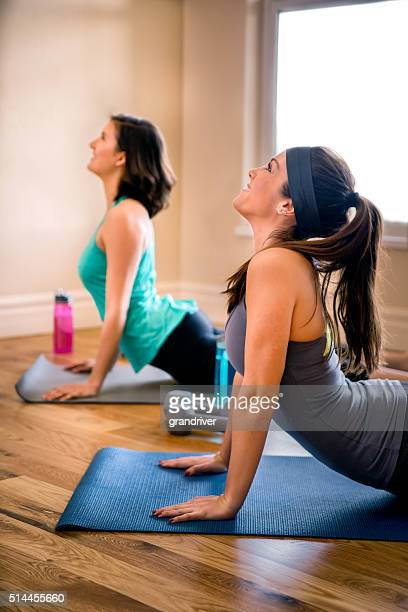 Two Young Women Doing Yoga Cobra Pose