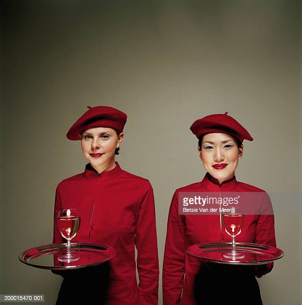 two young women dressed identically, holding wine glasses on trays. - red alert 2 stock pictures, royalty-free photos & images