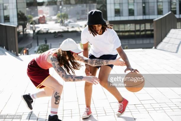 two young women dribbling a basketball - gender role fotografías e imágenes de stock