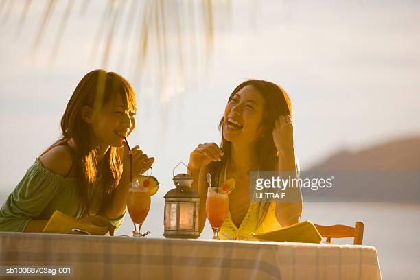Two young women drinking cocktails outdoors