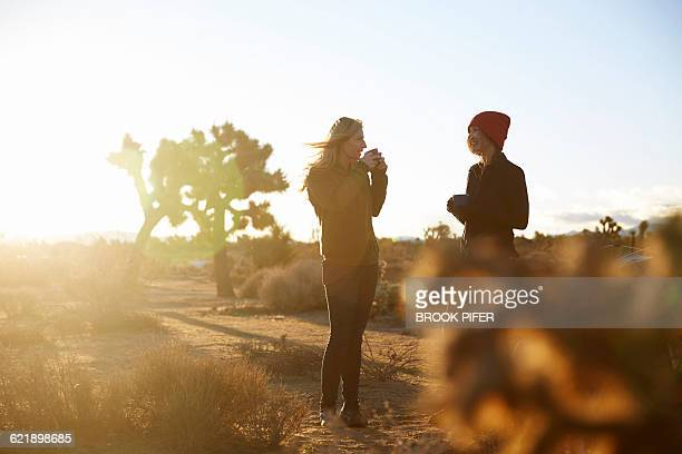 Two young women drinking coffee at campsite
