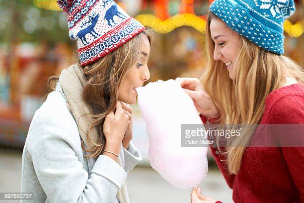 Two young women eating candy floss at funfair, outdoors