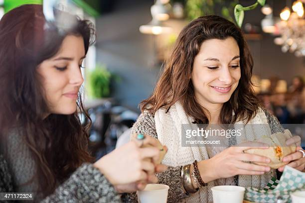 Two young women eating lunch at a restaurant throught window.