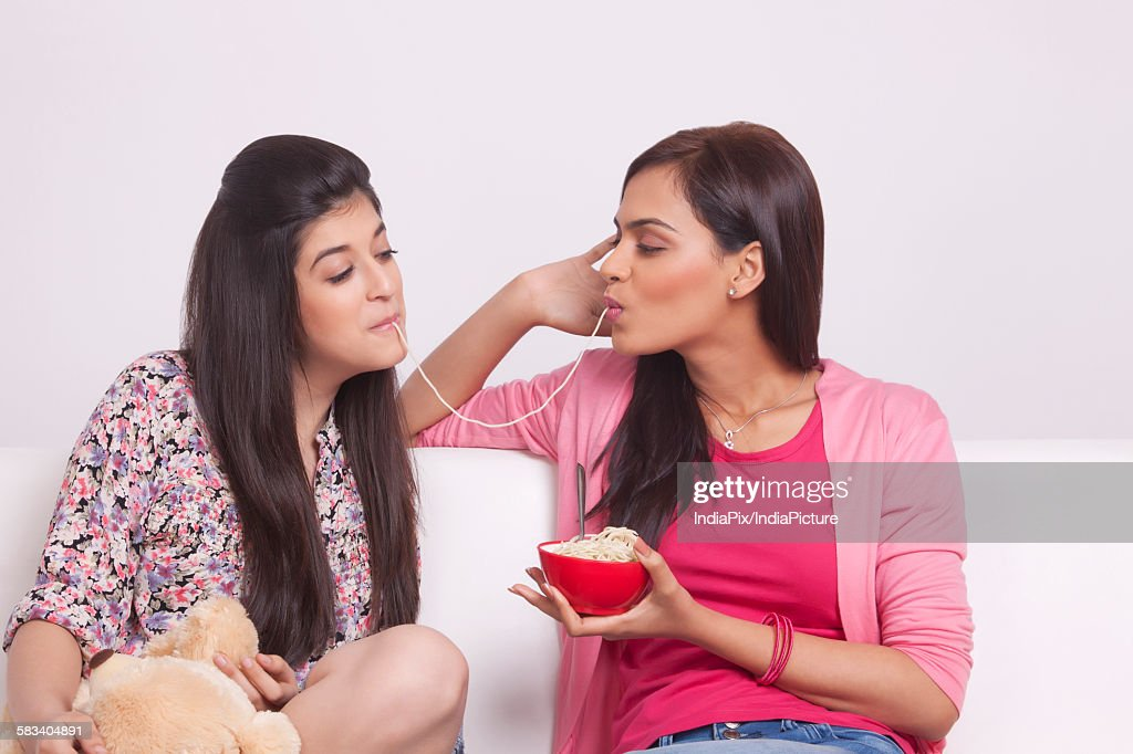 Two young women eating noodles : Stock Photo