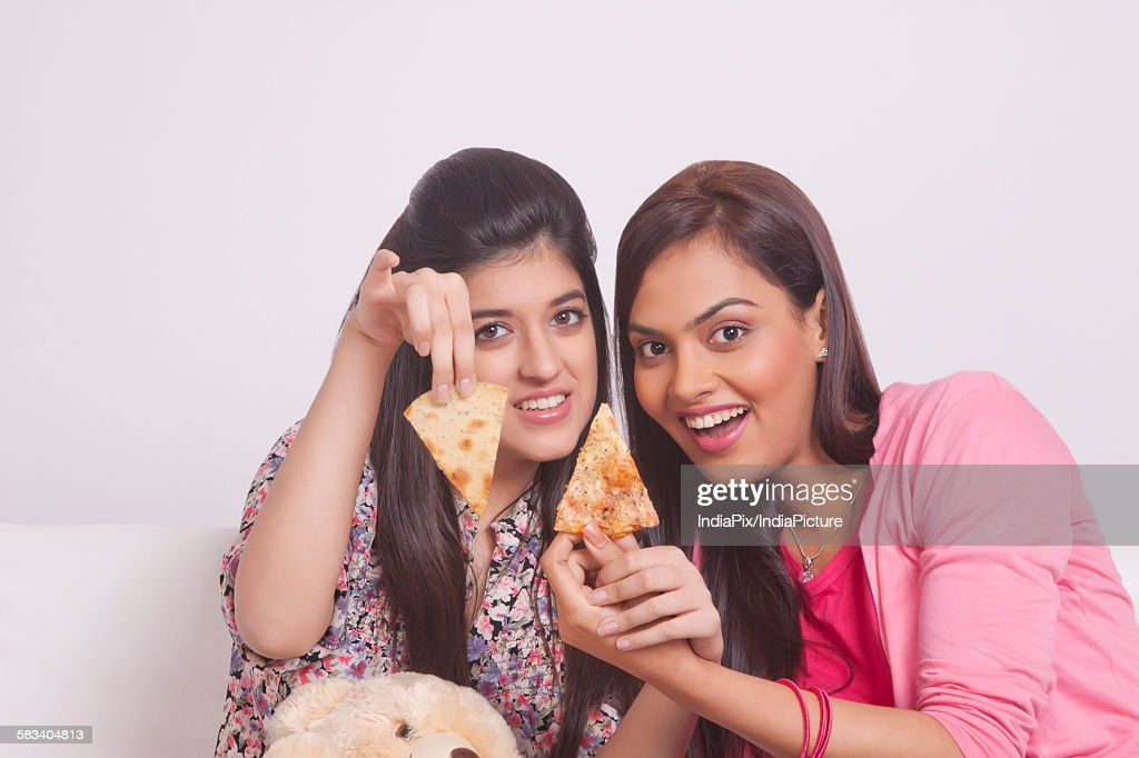Two young women eating pizza : Stock Photo