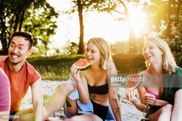 Zwei junge Frauen Essen Wassermelone mit Freunden am Grill