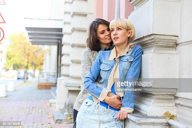 Two young women embracing and leaning back on building