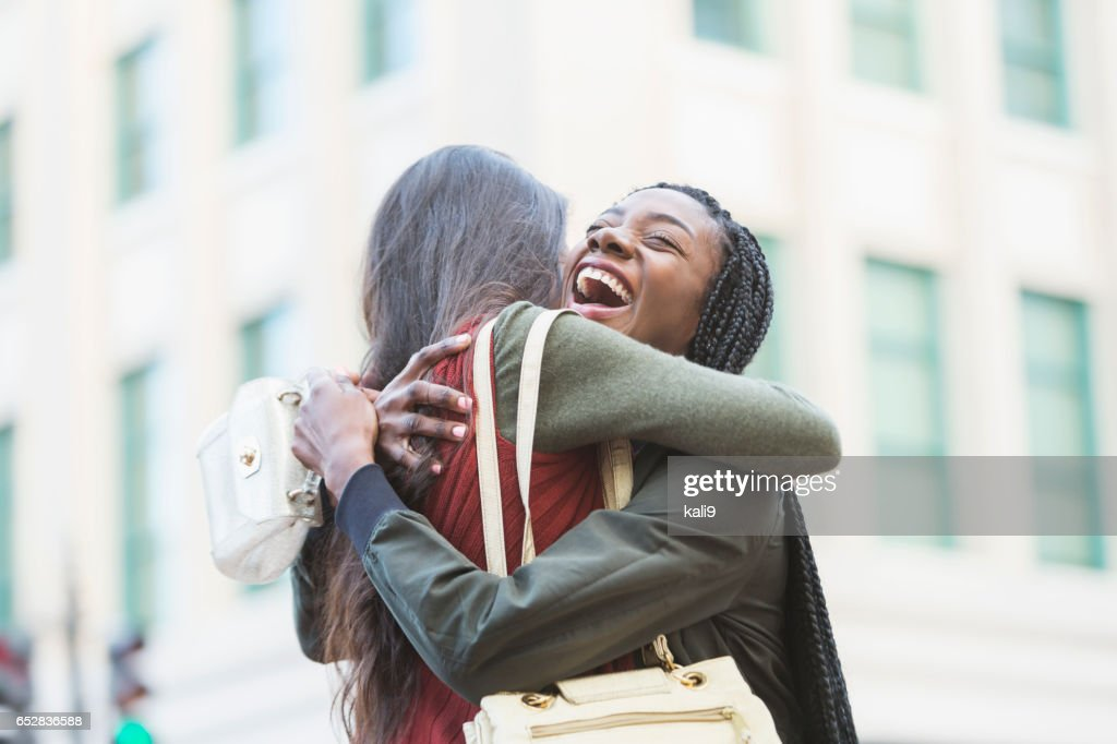 Two young women embracing on street corner : Stock Photo