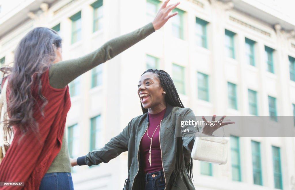 Zwei junge Frauen an Straßenecke umarmen : Stock-Foto