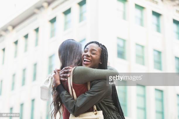 deux jeunes femmes embrassant sur coin de rue - passer le bras autour photos et images de collection