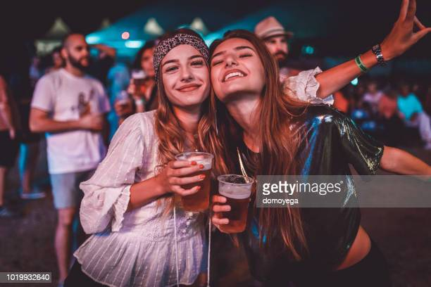 two young women enjoying a night at the music festival - teenage girls stock pictures, royalty-free photos & images