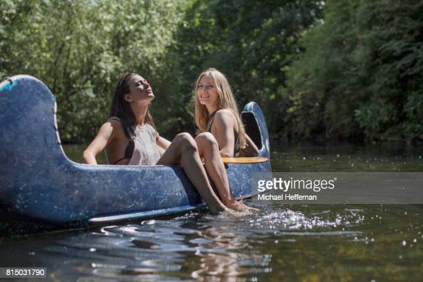 two young women enjoying canoe on a river - women sunbathing stock photos and pictures