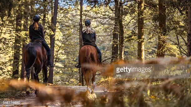 Two young women enjoying horseback riding